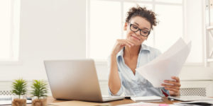 Woman with laptop looking at papers